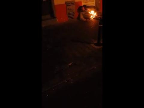 man engulfed in flames on a busy city street in the Balkans